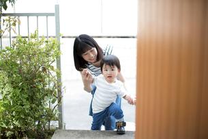 手をつないで家に入ろうとする幼児と母親の写真素材 [FYI01795479]