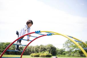 公園の遊具で遊ぶ小学生の男の子の写真素材 [FYI01795505]
