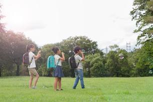 草原でシャボン玉を飛ばして遊ぶランドセルを背負った小学生達の写真素材 [FYI01795509]