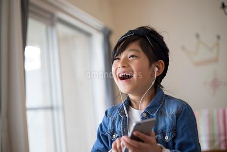 スマホで音楽を聴く小学生の女の子の写真素材 [FYI01795511]