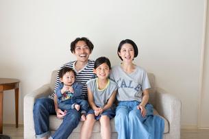 ソファーに座って微笑む家族の写真素材 [FYI01795664]