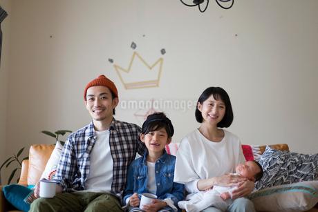 リビングのソファーに座ってくつろぐ家族の写真素材 [FYI01795718]