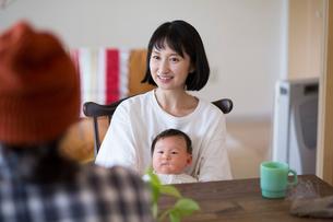 あかちゃんを膝に座らせている母親とそれをみている父親の写真素材 [FYI01795748]