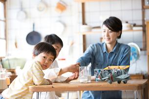 キッチンのテーブルでおやつを食べる兄弟と母親の写真素材 [FYI01795810]