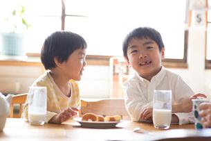 キッチンテーブルでおやつを食べる兄弟の写真素材 [FYI01795827]