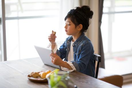 おやつを食べながらタブレットを操作する小学生の女の子の写真素材 [FYI01795851]