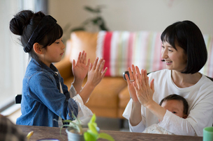 あかちゃんを膝に座らせている母親と小学生の女の子の写真素材 [FYI01795892]