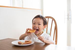 テーブルでおやつを食べる男の子の写真素材 [FYI01795905]
