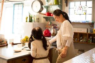 キッチンでお茶の用意をする女の子と母親の写真素材 [FYI01795922]