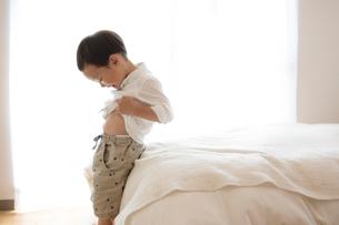 シャツをめくって自分のお腹を見る男の子の写真素材 [FYI01795965]
