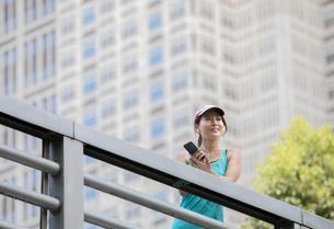 高層ビルの前でスマホを見るジョギング中の女性の写真素材 [FYI01795986]