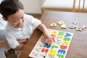 英語の知育玩具で英語の学習をする男の子とそれを手伝う母親の写真素材 [FYI01796008]