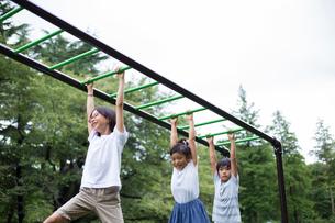 うんていをする小学生の子供たちの写真素材 [FYI01796025]