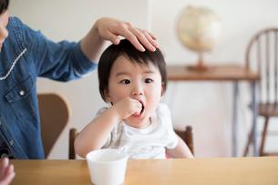 おやつを食べている子供と頭をなでる母親の写真素材 [FYI01796028]
