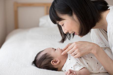ベッドの上に仰向けで寝ている赤ちゃんをあやす母親の写真素材 ...