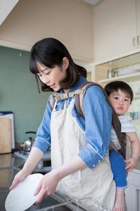 子供をおぶってキッチンで食器を洗う母親の写真素材 [FYI01796047]