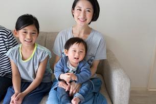 ソファーに座って微笑む家族の写真素材 [FYI01796071]