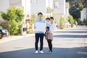家の前の路上で白ボードを持つ夫と赤ちゃんを抱いて微笑む妻の写真素材 [FYI01796077]