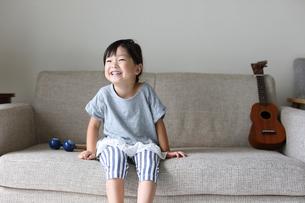 ソファーに座る小さな女の子の写真素材 [FYI01796080]