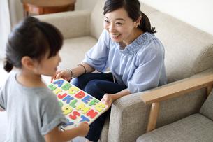 アルファベットのパズルを母親に見せる女の子の写真素材 [FYI01796101]