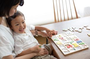 英語の知育玩具で英語の学習をする男の子とそれを手伝う母親の写真素材 [FYI01796108]