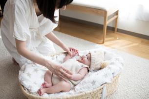リビングルームのクーファンで寝ている赤ちゃんとあやす母親の写真素材 [FYI01796111]