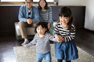 手をつないでリビングを歩く小さな姉妹とそれを後ろから見て微笑む両親の写真素材 [FYI01796143]