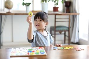 アルファベットのパズルをする女の子の写真素材 [FYI01796147]