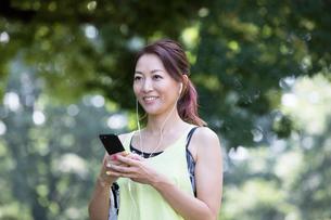 イヤホンをしながらスマホを見るジョギング中の女性の写真素材 [FYI01796152]