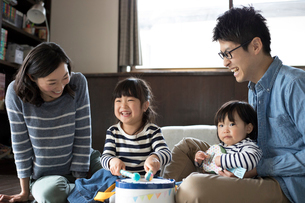 手作りの楽器のおもちゃで遊ぶ姉妹とそれを見守る両親の写真素材 [FYI01796171]