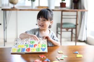 アルファベットのパズルで遊ぶ女の子の写真素材 [FYI01796184]