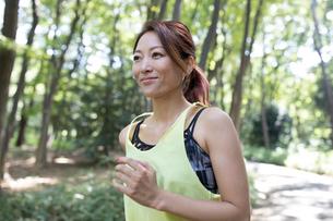 木立の中をジョギングする女性の写真素材 [FYI01796225]