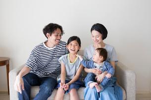 ソファーに座って微笑む家族の写真素材 [FYI01796237]