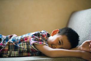 ソファーに寝転ぶ小学生の男の子の写真素材 [FYI01796251]