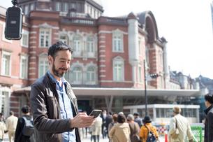 東京駅の近くでスマホで見ている外国人観光客の写真素材 [FYI01796264]