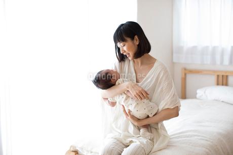 ベッドの上に座り赤ちゃんを抱く母親の写真素材 [FYI01796266]