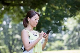 イヤホンをしながらスマホを見るジョギング中の女性の写真素材 [FYI01796278]