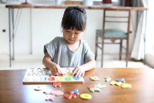 アルファベットのパズルで遊ぶ女の子の写真素材 [FYI01796300]
