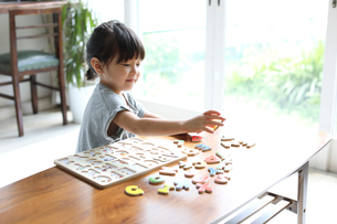 アルファベットのパズルで遊ぶ女の子の写真素材 [FYI01796301]
