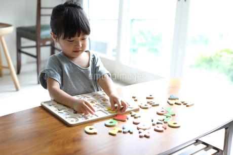 アルファベットのパズルで遊ぶ女の子の写真素材 [FYI01796302]