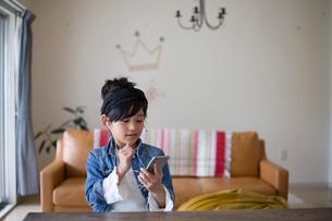 スマホで音楽を聴く小学生の女の子の写真素材 [FYI01796309]