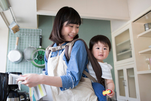 子供をおぶってキッチンで食器を洗う母親の写真素材 [FYI01796349]