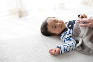 昼寝する赤ちゃんに添い寝する母親の写真素材 [FYI01796353]
