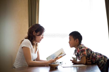 リビングルームで母親に勉強を教わる小学生の男の子の写真素材 [FYI01796357]