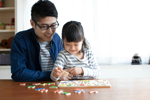 アルファベットのパズルをする女の子とそれを手伝う父親の写真素材 [FYI01796391]