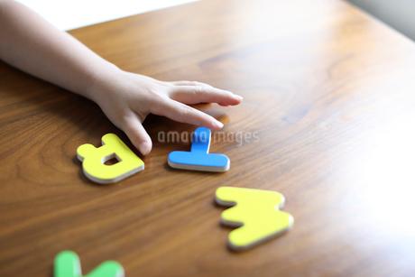 アルファベットのパズルを持つ子供の手の写真素材 [FYI01796427]