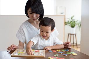 英語の知育玩具で英語の学習をする男の子とそれを手伝う母親の写真素材 [FYI01796428]