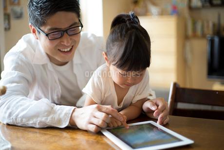 タブレットを使う女の子と父親の写真素材 [FYI01796448]