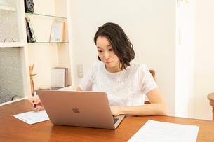ノートパソコンで仕事をしながら書類に記入する女性の写真素材 [FYI01796470]