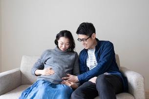 妊婦の妻のお腹に手をあてる夫の写真素材 [FYI01796473]